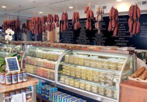 A photograph of the checkout and deli counter at Bricco Salumeria.