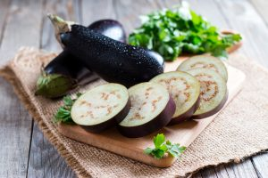 A photograph of sliced eggplant on a cutting board, with full eggplants in the background.