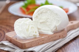 A photograph of mozzarella cheese on a wooden cutting board.
