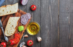 Fresh baguette sliced into pieces, tomatoes, vegetables and olive oil, ingredients for making a vegan sandwich, close-up. Dark wooden background, copy space for text