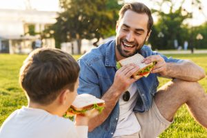 A father and son enjoy sandwiches on a grassy field during a sunny day.