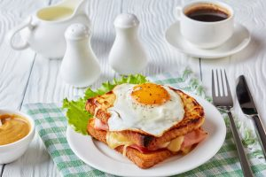 A croque madame sandwich on a plate over a checkered napkin. A fork and knife lay off to the right side, while tea and seasoning jars can be seen above.