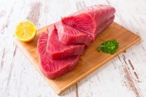 Several slices of raw tuna can be seen on a cutting board on a white tabletop. Half of a lemon can be seen to its left, and a small pile of collared greens to the right.