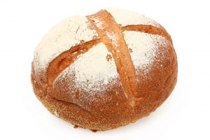 A close up of a round loaf of white mountain bread.