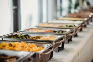 A close up of a line of catering platters filled with food on a white tabletop. Only two are in focus. The one closest to the camera has potatoes in it, and the one furthest from the camera is filled with an assortment of vegetables.